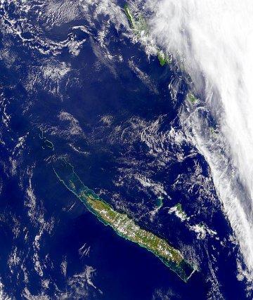 Alors qu'une importante masse nuageuse commence à recouvrir l'archipel du Vanuatu on distingue bien la Nouvelle Calédonie. Si la Grande Terre n'est que perlée par quelques bandes nuageuses, les Iles Loyauté, en particulier Maré et Lifou, disparaissent sous le blanc des nuages.