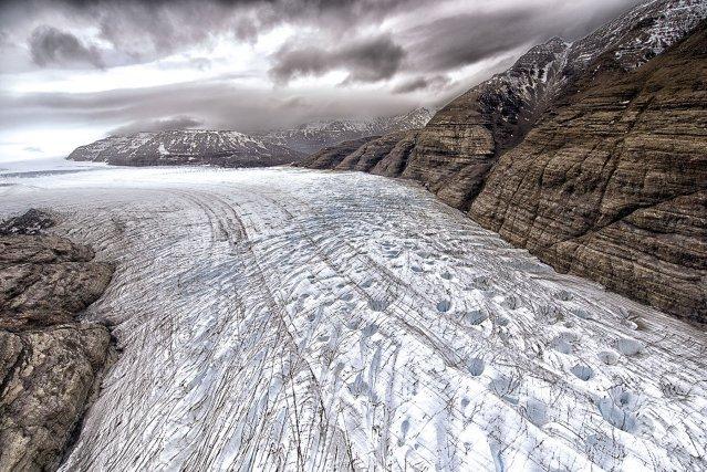 Vue du glacier Ampère, situé au sud-ouest des Kerguelen, la langue terminale du glacier Ampère présente une surface chaotique, formée de brèches et de failles profondes contenant des morceaux de roches arrachés aux versants du sud-est de la calotte Cook. Cette région de l'île rarement visitée par l'homme, en dehors de quelques missions scientifiques, est si exposée aux tempêtes qu'elle n'est complètement dégagée que quelques jours par an.