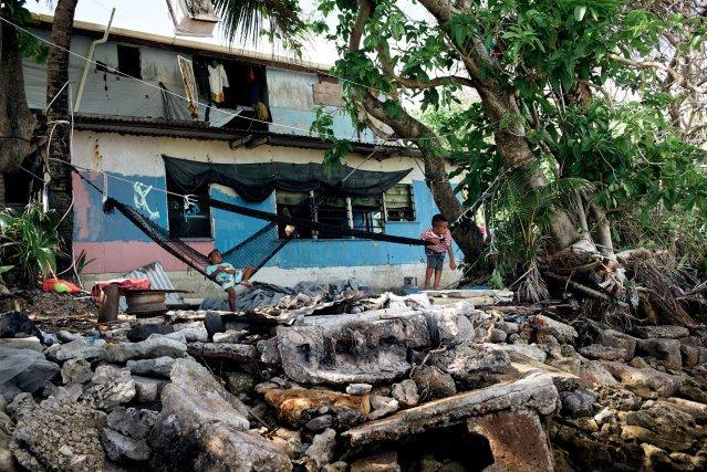 En 2015, la houle du cyclone Pam a détruit la digue de cette maison à Luapou. La famille ne prend plus la peine de nettoyer car elle fait face à de nouvelles tempêtes chaque année. De nombreux habitants cherchent à immigrer en Nouvelle-Zélande, qui limite l'accueil à 75Tuvaluans chaque année. Selon un rapport de 2016 de la Banque mondiale, la quantité de migrants continuera d'augmenter fortement en raison des problèmes de réchauffement. Mais aucun État ne reconnaît le statut de réfugié climatique.