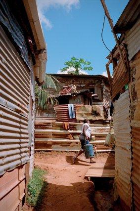 Jean vit à Piste Tarzan avec sa femme et sa sœur. En attente de régularisation, il espère pouvoir quitter le quartier pour offrir de meilleures conditions de vie à sa famille