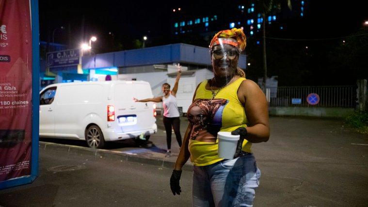 Avec bonne humeure, et visière sur le front, Sandra et Moni distribuent les soupes aux démunis installés devant le CHU de Pointe-à-Pitre, Guadeloupe.