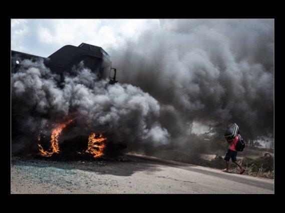 Un camion brûle à l'entrée du chantier de Belo Monte, alors qu'un travailleur quitte les lieux après la grève. Novembre 2012.
