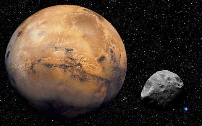 Reconstitution du globe de Mars à partir des images prises par les orbiteurs Viking. au centre le gigantesque canyon, Valles Marineris,  découvert par Mariner-9 en 1972. Cette vallée est profonde par endroit de 8 à 9 km et longue  de plus de 4000 km.  A gauche  les trois volcans de Tharsis. Au premier plan, le satellite de Mars, Phobos