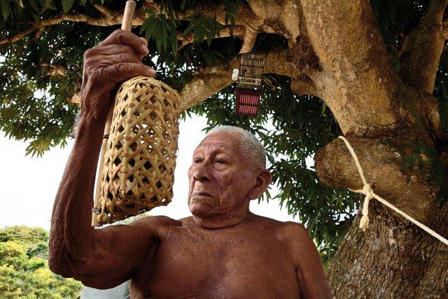 Albert Blaise, Awala. À 93 ans, Monsieur Blaise pratique encore la vannerie. Il tient en main un kalawasi, le hochet en arouman avec des graines de laurier jaune utilisé par les femmes pour danser et chanter lors des fêtes de lever de deuil.