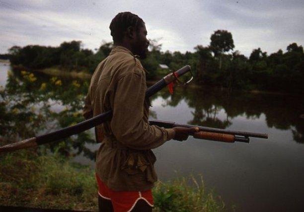 Langa Tabiki. Dans cette île en forme de base arrière des Jungle Commando, à dix heures de pirogue en amont de Saint-Laurent du Maroni, une sentinelle monte la garde équipée d'un fusil à pompe et d'un simple sabre. 1986