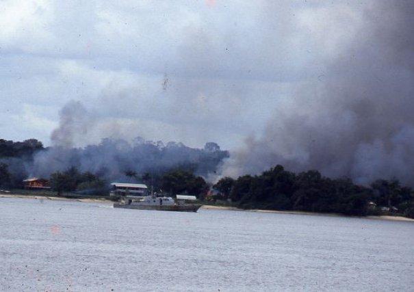 Attaque d'Albina. Les Jungle Commando n'hésitent pas à attaquer la ville frontière avec la Guyane, ici en feu, malgré les ripostes de la vedette de l'armée du Suriname à la mitrailleuse et au canon. 1986