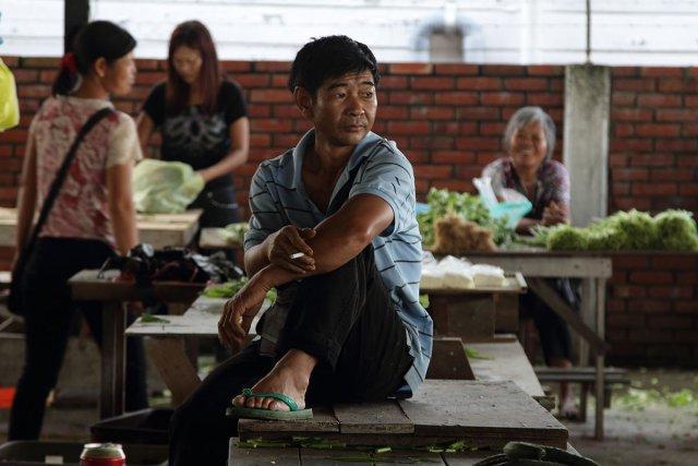 Au marché chinois de Paramaribo, un agr.iculteur chinois fume une cigarette. 2012.