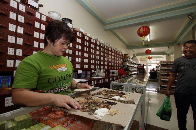 Foeng Paw, l'assistante d'un herboriste chinois. prépare une prescription à la pharmacie Soeng Ngie & Co. Février 2013.