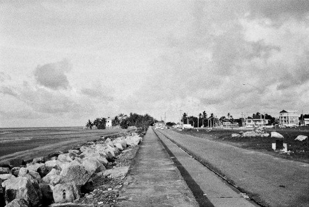 """▲Le """"seawall """", digue érigée par les anglais à la fin du 19ème siècle protège Georgetown de l'érosion marine. La ville est en effet construite en-dessous du niveau de la mer. Tour à tour, Daron Jones et Mona-Lisa Allen évoquent avec ironie la fragilité de Georgetown et du Guyana, qui en plus de voir ses richesses pillées (or, diamant, bauxite, manganèse, bois, etc.), se retrouve également à la merci des flots ..."""