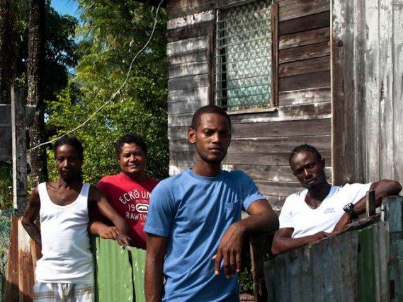 """Daron Jones (au centre) et son frère Franck (à gauche) évoquent avec amertume les conditions de vie difficiles à Georgetown : gel des salaires, corruption, chômage, gouvernement qui reste sourd face aux inégalités sociales. Quand ils parlent du Président du Guyana, ils ne disent pas (Donald) Ramotar mais """" Rhum and tar """" ("""" Rhum et goudron """")."""