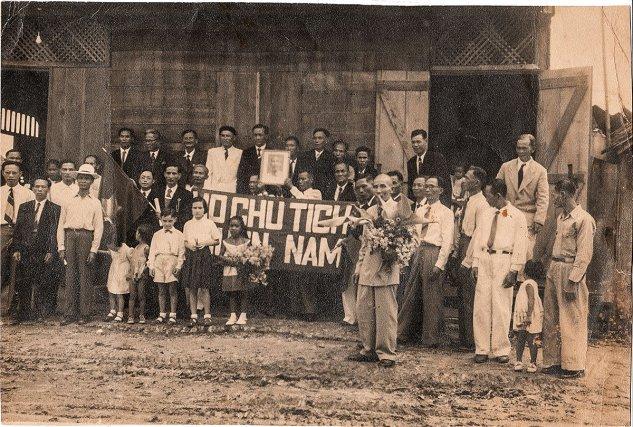 """Ex-bagnards  fêtant le Nouvel An chinois au village """"chinois"""" de Cayenne. Début des années 1950. Sur la banderole : """"Vive le président Ho""""."""