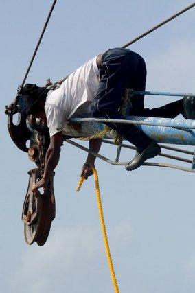 Un matelot change les câbles du chalut, au bout des tangons du crevettier