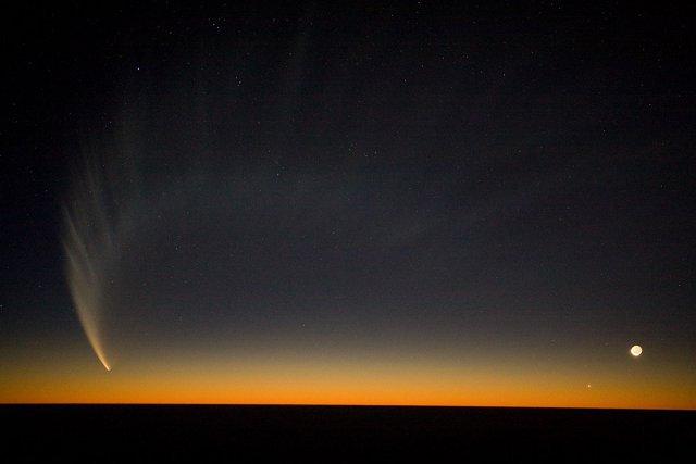 La queue de la comète McNaught sur le pacifique vue de l'observatoire VLT en janvier 2007. La lune est visible sur la droite.