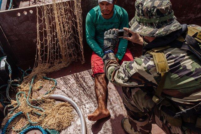 Après l'assaut d'une tapouille par le GIGG (Groupe d'intervention de la gendarmerie de Guyane), un pêcheur illégal est pris en photo par l'officier en second de la Gracieuse, l'un des quatre navires de la marine nationale en charge de la surveillance des eaux guyanaises.