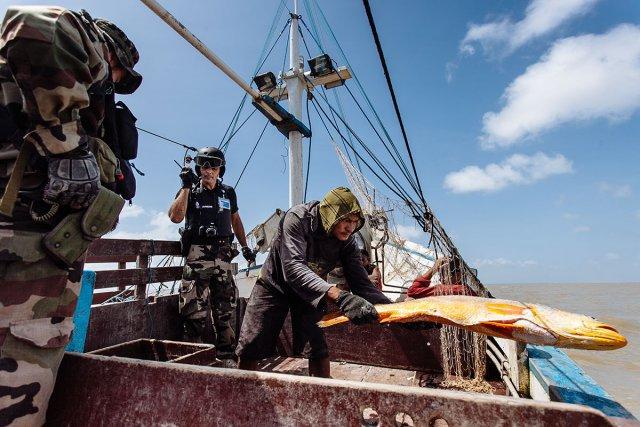 Sous le contrôle d'un homme de la marine et d'un autre de la gendarmerie maritime, l'un des sept membres de l'équipage jette par-dessus bord la cargaison du bateau. Sur cette tapouille prêt d'une tonne de poissons – pour la plupart de belles pièces - sera rejetés par mesure d'hygiène.
