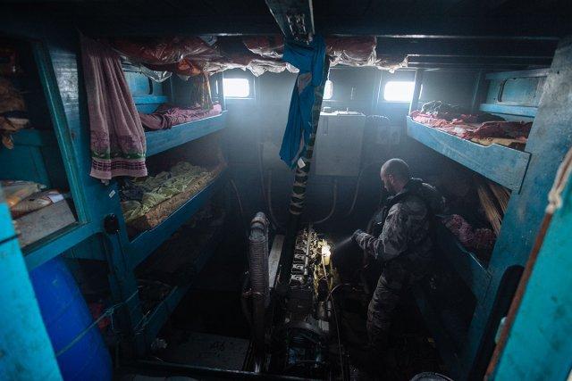 Un des hommes de la Marine inspecte le moteur d'une tapouille arraisonnée. Ceux-ci sont souvent sabotés par l'équipage dans une ultime tentative pour éviter que le bateau ne soit confisqué. La salle abritant ce moteur bruyant et poisseux est aussi souvent l'espace de repos des pêcheurs.
