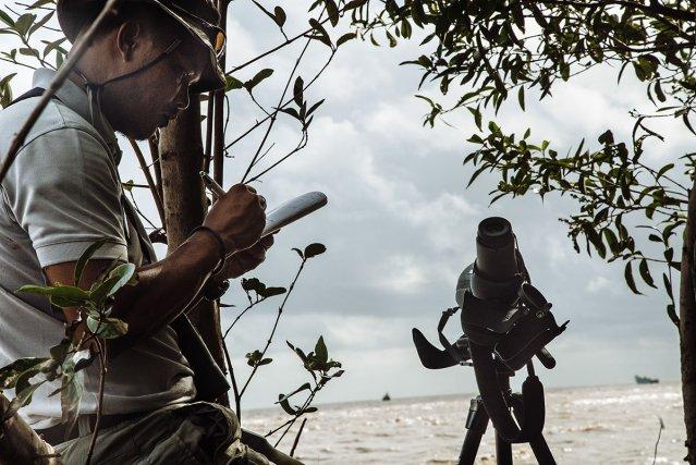 Un garde assermenté de la réserve de l'Amana prend des photos note les numéros d'immatriculation de trois tapouilles surinamaises en situation de pêche illégale.