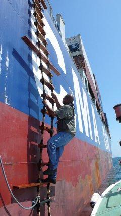 Conor Mandé sur l'échelle de corde du porte-conteneur Herodote. 2009.