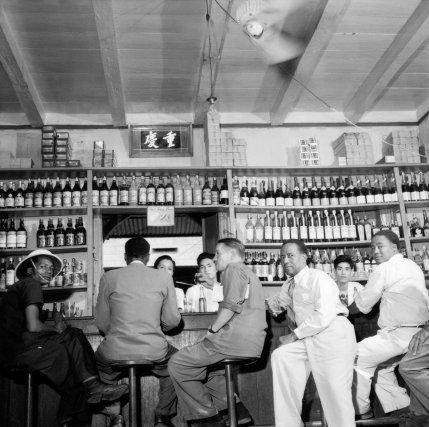 Dans un bar, les Chinois sont assez nombreux en Guyane Française et s'occupent surtout de commerce, genre débit de boissons. Beaucoup ignorent leur langue d'origine. Ils tiennent les boutiques, épiceries, blanchisseries, débits de boissons particulièrement fréquentés. Consommation de base: le rhum, d'importation martiniquaise.