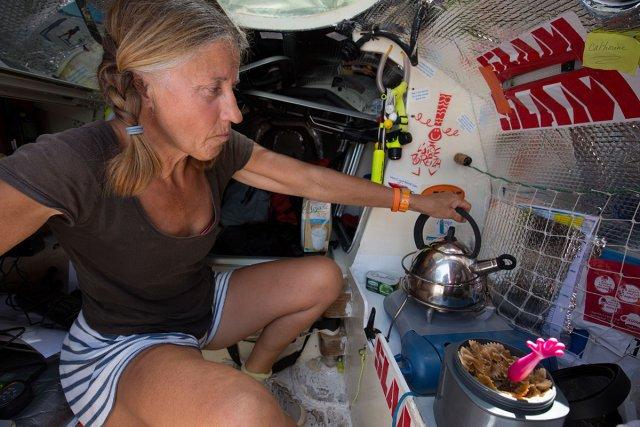 """À l'image de Catherine Barroy, chaque skipper s'est aménagé un """"coin cuisine"""" à bord de son embarcation. Reste que l'instabilité constante et l'exiguïté du lieu rendent souvent la préparation des repas particulièrement périlleuse. Catherine Barroy, 60 ans."""