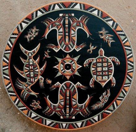 Œuvre de Minestelli Ananuman. Les motifs représentent mulokot, l'esprit des eaux (à gauche), tokokosi, la chenille à deux têtes (en bas) et kuliputpë, la tortue (à droite). Au centre sont symbolisées les épines de l'arbre fromager.