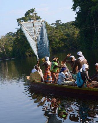 Des membres de la famille Aboikoni dansent sur une pirogue du village. Dans le cadre du rituel, la pirogue exécute plusieurs cercles dans l'eau pour représenter les hésitations de l'âme du mort. Asindoopo, Suriname.