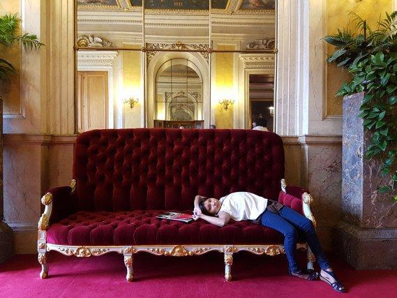 Blandine se repose sur l'un des sofas d'un salon du Sénat.