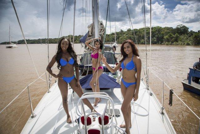 3 candidates au concours de miss Guyana posent sur le pont d'Atla, le plus grand bateau du rallye (18m)