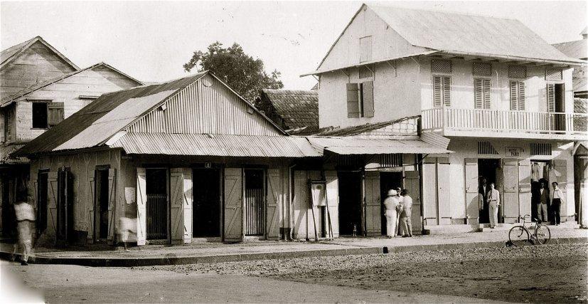 Carte postale de la place du Marché à Cayenne en 1937. à droite, le magasin «Petit Paris», avait été construit par le père de Simon Raad en 1936. Devant la porte à gauche de l'immeuble, en premier plan, Rachid Saba (du Suriname), et derrière lui, Joseph Chaoul. Devant la porte de droite, en premier plan, Chalita Raad, et derrière lui Richard Khalil Chaïa.