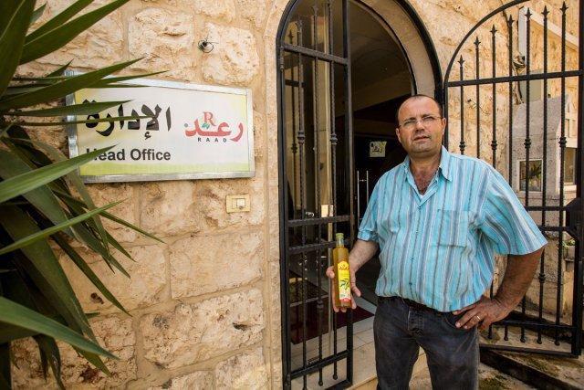 Jean Raad devant ses produits locaux, olives et condiments.
