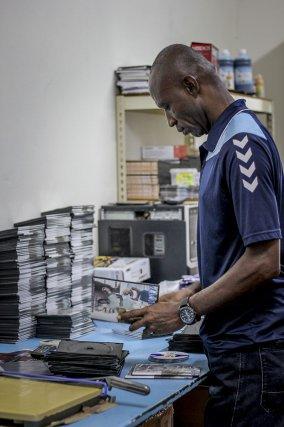 Un employé du Sunil's DVD shop empaquète des DVD gravés.