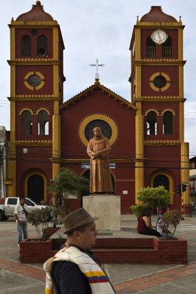 Un homme avec un poncho aux couleurs de la Colombie passe devant la statue de Fray Alfonso Pena Barrios qui est face à l'église du parc central de Yumbo. Valle del Cauca.