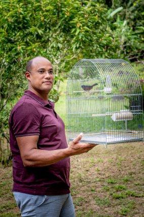 Vinh San Lao, éleveur passionné pose dans son jardin à Rémire. Il connaît chacun de ses oiseaux, leur tempérament, leurs habitudes.