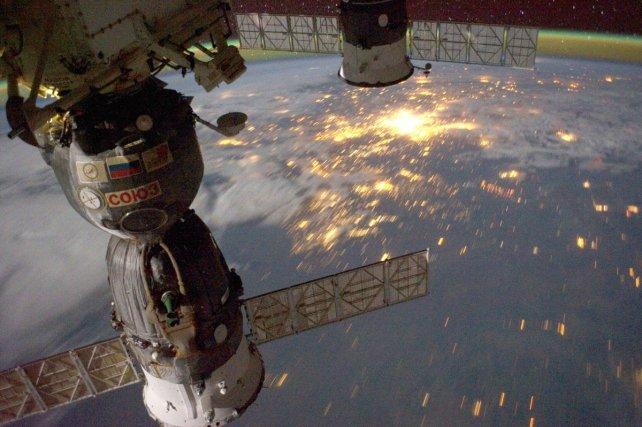 La nuit vue depuis la station spatiale ISS (2011). A gauche, les modules Soyouz sont arrimés en attendant la descente des cosmonautes sur terre.