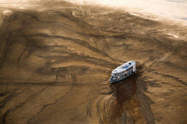 Sécheresse de l'Amazone en 2005. Ce bateau échoué à l'Est de Manaus reflète l'isolement des communautés vivant au bord du fleuve pendant la sécheresse, dépendantes de l'approvisionnement aérien (cette photo de Daniel Beltrà a été primée au World Press en 2007).