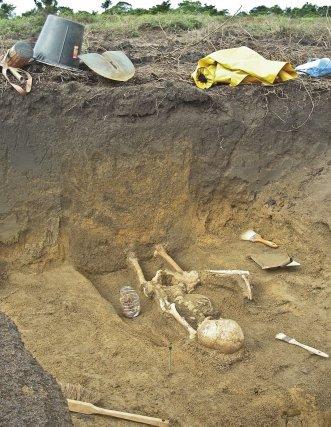 La coupe montre que le couvercle du cercueil a cédé sous la pression des sédiments.
