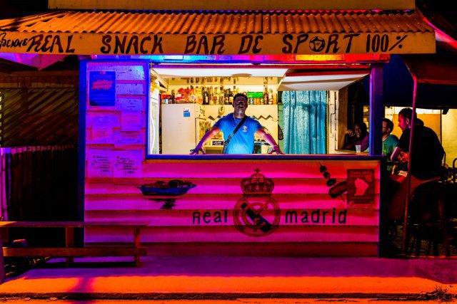 Etienne Kouakou. Sur la place des fêtes de Maripa-Soula, le Bar des sports est un lieu central où se croisent toutes les générations. Supporter inconditionnel du Real Madrid, étienne Kouakou ne manque pas de diffuser un match de foot et aime débattre des qualités des autres clubs. étienne connaît tout de Maripa-Soula et se fait un point d'honneur à échanger avec les touristes sur la vie du fleuve.