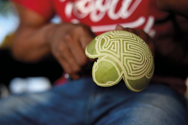 Jeune artisan du village travaillant une calebasse.