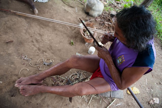 Renaud monte la corde sur l'arc. C'est une longue opération car la corde arrimée à l'une des poupées, est ensuite fixée sur le bois avant de finir ancrée à la deuxième poupée.