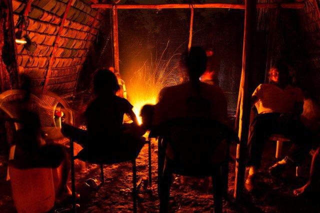 Une communauté Waorani lors du repas du soir sous une hutte traditionnelle. Aujourd'hui, pour bien des éléments de confort, le bois a cédé la place au plastique ou au béton !