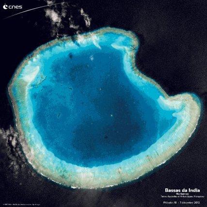 Voici l'une des dernières photos de voyage du satellite Pléiades 1B : l'atoll Bassas da India. L'atoll Bassas da India fait partie des Terres australes et antarctiques françaises et se trouve au large de la côte africaine, entre le Mozambique et l'île de Madagascar. C'est une immense barrière de corail  circulaire, de 12 km de diamètre, qui encercle un lagon de faible profondeur. Sur cette image, immortalisée par le satellite Pléiades 1B, la corolle grise qui entoure l'atoll est une bande de sable qui s'est accumulée à l'arrière du récif, le cercle bleu turquoise correspond à la barrière de corail et le cœur bleu foncé, au lagon.